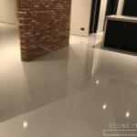 Pavimento in resina autolivellante bicomponente, con una finitura lucida, colore Ral 9010.